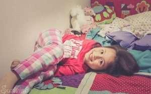 niña en cama sonriendo para hablar de madrugar para la vuelta al cole y cambio de hora y sueño infantil