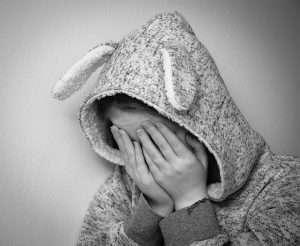 niña con la cara tapada acoso agobio llorar pena