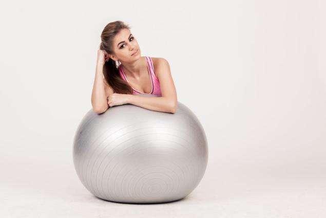 mujer sobre pelota gigante para hablar de pilates en el embarazo