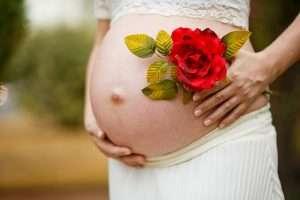 tripa de embarazada con una flor encima, para hablar de cuidados de belleza en embarazo