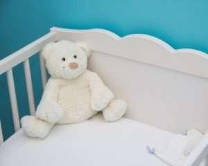 foto de una cuna con un osito para hablar de cómo elegir la cuna del bebé y como pasarle d e la cuna a la cama
