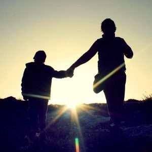 imagen de un adulto y un niño al anochecer para hablar de ayudas para las familias monoparentales