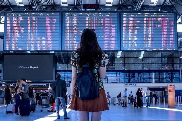 mujer mirando aviones para hablar de viajar enfermo en el extranjero