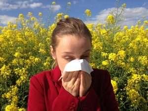 mujer estornudando entre margaritas para hablar de alergia al polen