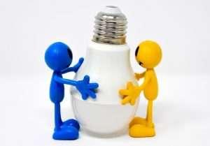 dos muñequitos sujetan una bombilla para hablar de web sobre el Bono Social de la Luz y de la denuncia de la FEFN sobre el bono social de la luz