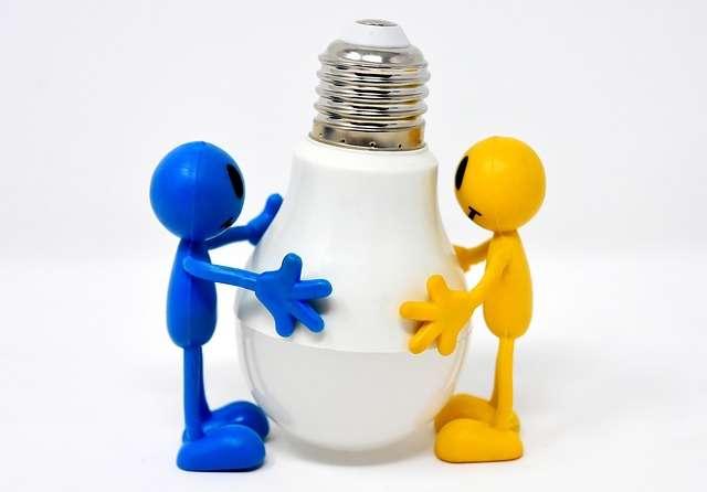 dos muñequitos sujetan una bombilla luz