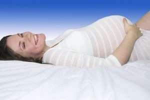 embarazada tumbada feliz para hablar de las hormonas del embarazo