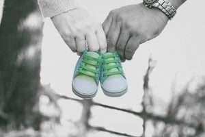 dos manos sujetando zapatitos de bebé para hablar de día del libro 2018: libros maternidad y crianza