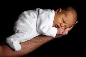 bebé boca abajo apoyando tripa en brazo de su padre para hablar de aliviar los gases en el bebé