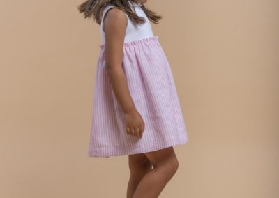 Vestido niña combinado de algodón blanco y falda rosa a rayas, tallas 3 a 10 años (Laranjinha, 38 €).