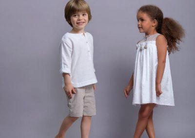 Niño con camisa cuello mao de lino(36,50 €) y bermuda lino arena (42,50 €) y niña con vestido en blanco y beige (75 €), en tallas 3 a 10 años, todo de Laranjinha.