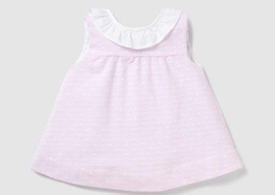 Vestido en color rosa, sin mangas y cuello babero a contraste. Lleva el cierre en la espalda mediante botones y frunce en el canesú. Talla 3 a 36 meses (dulces en el corte inglés, 29,90 €)